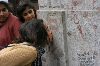Chica besando la tumba de Oscar Wilde
